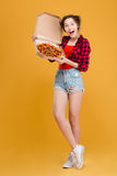 Funny joyful young woman standing and posing with pizza Stock Image