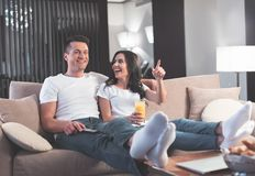 Carefree loving couple watching TV at home. It is funny. Joyful young women is pointing finger at television set and laughing. She is sitting on sofa and Stock Photo