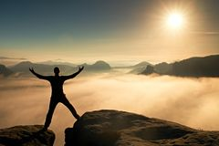 Funny jumping hiker in black celebrate triumph. Stay between two rocky peaks. Wonderful misty daybreak. Royalty Free Stock Photography