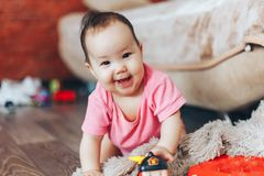 little baby starting to crawl at home in pink clothes royalty free stock image