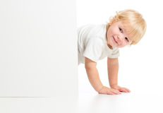 Funny kid on all fours behind banner Royalty Free Stock Photo