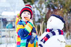 Funny kid boy in colorful clothes making a snowman Royalty Free Stock Images