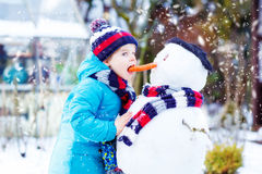 Funny kid boy in colorful clothes making a snowman Royalty Free Stock Image