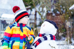 Funny kid boy in colorful clothes making a snowman Royalty Free Stock Photos