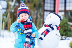 Funny kid boy in colorful clothes making a snowman, outdoors Royalty Free Stock Photography