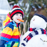 Funny kid boy in colorful clothes making a snowman, outdoors Royalty Free Stock Photos