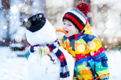 Funny kid boy in colorful clothes making a snowman, outdoors Stock Photos