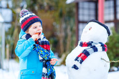 Funny kid boy in colorful clothes making a snowman, outdoors Royalty Free Stock Images