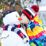 Funny kid boy in colorful clothes making a snowman, outdoors Stock Images