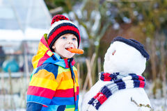 Funny kid boy in colorful clothes making a snowman, outdoors Stock Photography