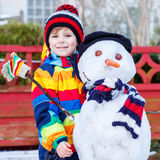 Funny kid boy in colorful clothes making a snowman Royalty Free Stock Photo