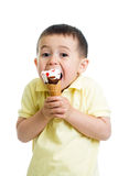 Funny kid boy eating ice cream in studio isolated Stock Photos
