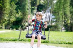 Funny kid boy having fun with chain swing on outdoor playground during rain. Child swinging on warm rainy summer day. Active leisure with kids. Happy crying stock images