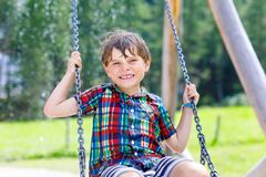 Funny kid boy having fun with chain swing on outdoor playground during rain. child swinging on warm rainy summer day. Active leisure with kids. Happy boy with royalty free stock photography