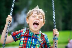 Funny kid boy having fun with chain swing on outdoor playground during rain. Child swinging on warm rainy summer day. Active leisure with kids. Happy crying stock photos