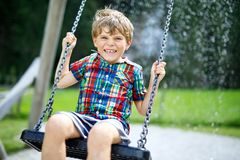 Funny kid boy having fun with chain swing on outdoor playground during rain. Child swinging on warm rainy summer day. Active leisure with kids. Happy crying stock photography
