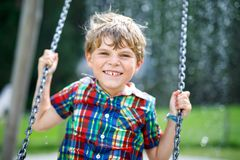 Funny kid boy having fun with chain swing on outdoor playground during rain. Child swinging on warm rainy summer day. Active leisure with kids. Happy crying royalty free stock photo