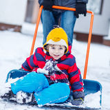 Funny kid boy having fun with riding on snow shovel, outdoors Stock Photo