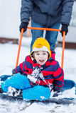 Funny kid boy having fun with riding on snow shovel, outdoors Royalty Free Stock Image
