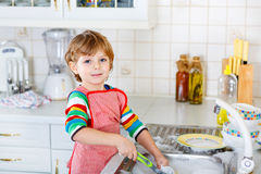 Funny kid boy helping and washing dishes at home Stock Photo