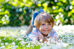 Funny kid boy laying on green grass in summer. Funny little blond child with blue eyes laying on the grass with daisies flowers in the park. On warm summer day Stock Images