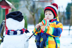 Funny kid boy making a snowman in winter Royalty Free Stock Image