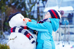 Funny kid boy making a snowman in winter Royalty Free Stock Images