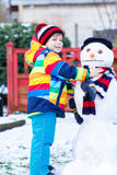 Funny kid boy making a snowman in winter Royalty Free Stock Photos