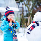 Funny kid boy making a snowman in winter outdoors Stock Photos