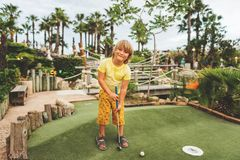 Funny kid boy playing mini golf Stock Images