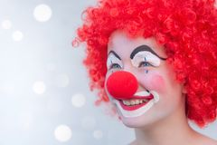 Funny kid clown laughing with red curly hair and red nose. Background bokeh, looking throug cardboard stock photography