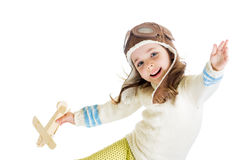 Funny kid dressed as pilot and playing with wooden airplane toy Stock Photos