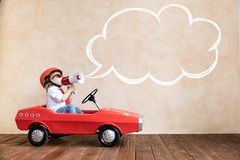 Funny kid driving toy car at home royalty free stock image