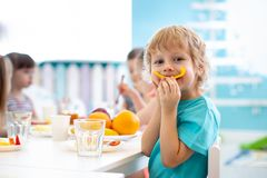 Funny kid eating fruits in kindergarten dining room royalty free stock photography