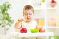Funny kid eating healthy food indoor Stock Photos