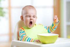 Funny kid eating healthy food indoor Stock Images