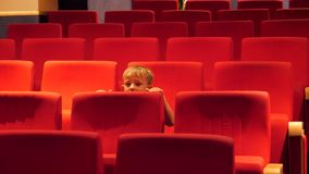 Funny kid in a empty cinema hall moving restless on a chair. UHD 4K stock video footage