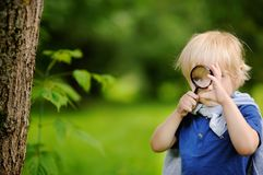 Funny kid exploring nature with magnifying glass. Little boy looking at tree with magnifier. Summer activity for inquisitive child royalty free stock images