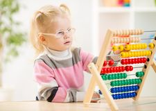 Funny kid in eyeglases counting using abacus Royalty Free Stock Photography