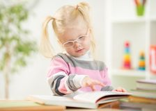 Funny kid in eyeglases reading book at home Stock Image
