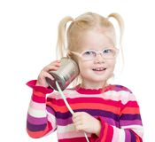 Funny kid in eyeglasses with can as a telephone. Funny kid in eyeglasses using a can as a telephone isolated on white Royalty Free Stock Photography