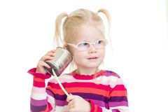 Funny kid in eyeglasses using a can as a telephone. Isolated on white Royalty Free Stock Photos