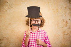 Funny kid with fake mustache. Happy child playing in home stock photo