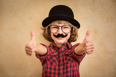 Funny kid with fake mustache. Happy child playing in home stock images