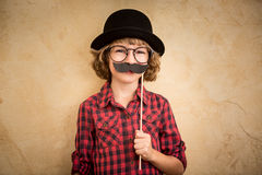 Funny kid with fake mustache. Happy child playing in home royalty free stock images