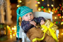 Funny kid on a festive background. Little funny baby in a hat dwarfs sitting on a chair with a gift in his hands, a set of bright festive lights in the Stock Images