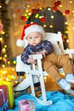 Funny kid on a festive background. A small funny kid in a Santa Claus hat sits on a chair, a set of bright festive lights in the background Stock Image