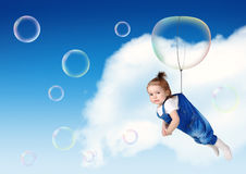 Funny kid fly on soap bubble, flight creative concept Royalty Free Stock Photography