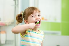 Funny kid girl brushing teeth in bathroom Stock Images