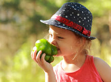 Funny kid girl in hat eating big green pepper Stock Images